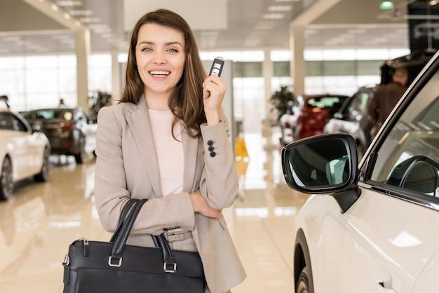 Belle femme tenant des clés de voiture dans la salle d'exposition
