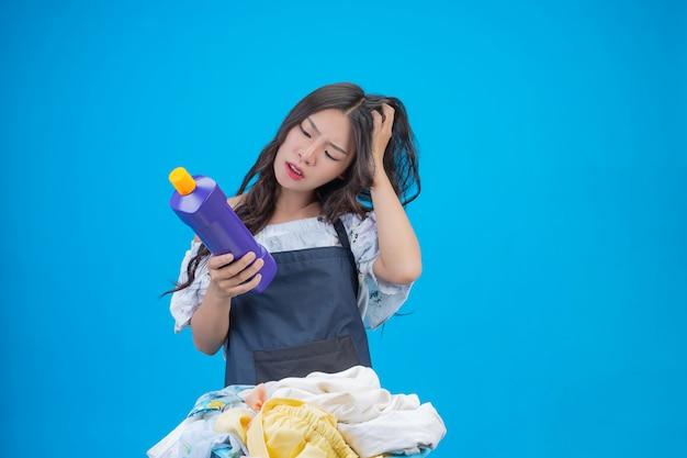 Belle femme tenant un détergent à lessive préparé sur bleu