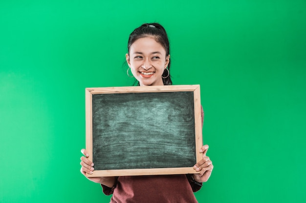 Belle femme tenant à deux mains tout en montrant quelque chose sur un tableau blanc tout en regardant à côté sur un mur vert