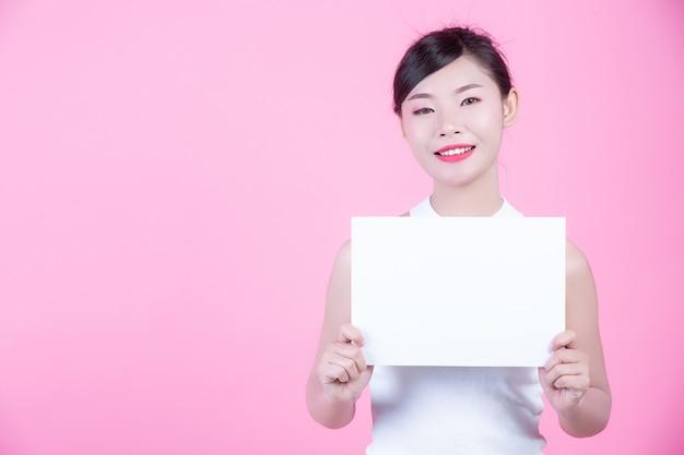 Belle femme tenant une feuille de tableau blanc sur un fond rose.