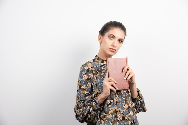 Belle femme tenant le livre étroitement.