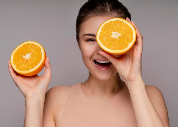 Belle femme tenant orange coupée en deux