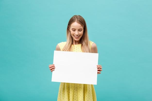 Belle femme tenant un panneau d'affichage vide isolé sur fond bleu