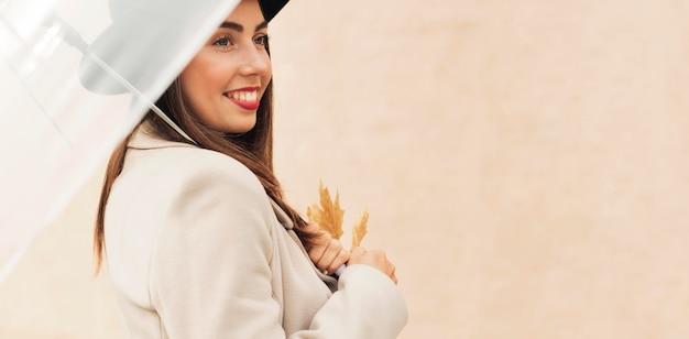 Belle femme tenant un parapluie transparent avec espace copie
