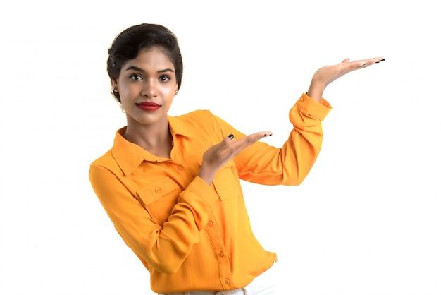 Belle femme tenant et présentant quelque chose dans la main avec un sourire heureux.