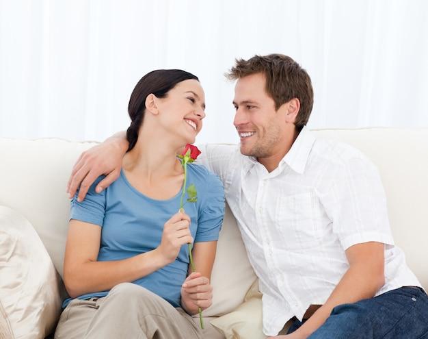 Belle femme tenant une rose assis sur le canapé