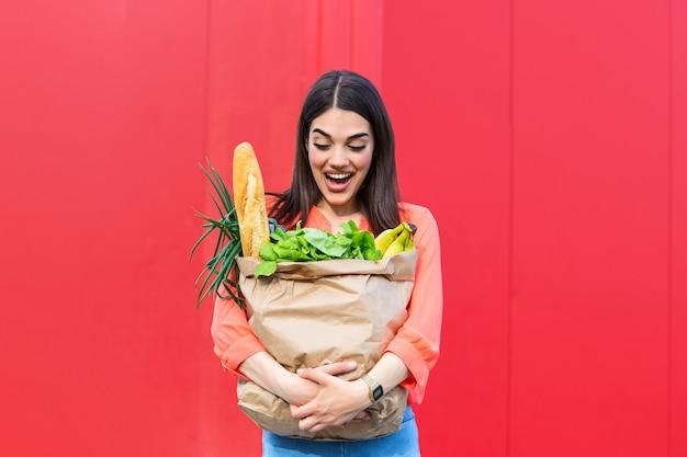 Belle femme tenant des sacs d'épicerie sur fond rouge