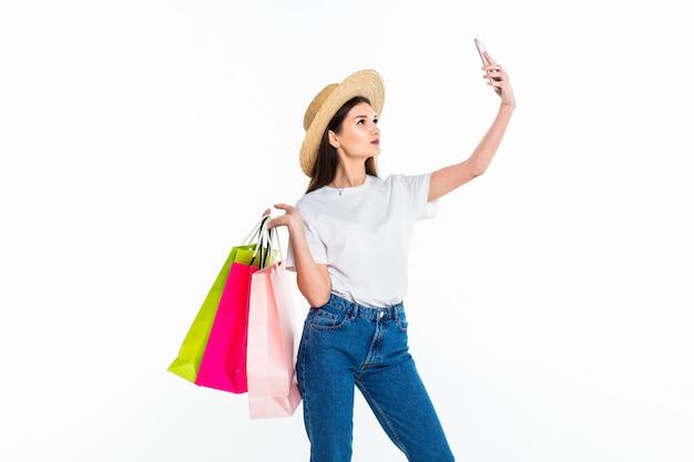 Belle femme tenant des sacs à provisions et prenant selfie avec téléphone portable isolé sur mur blanc