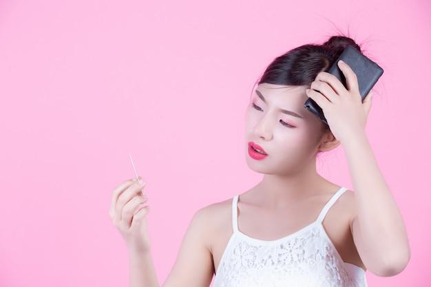 Belle femme tenant un smartphone et une carte sur un fond rose