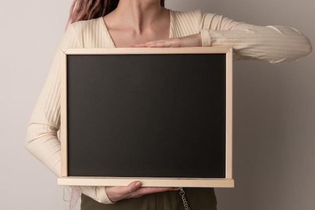 Belle femme tenant le tableau noir de craie sur blanc