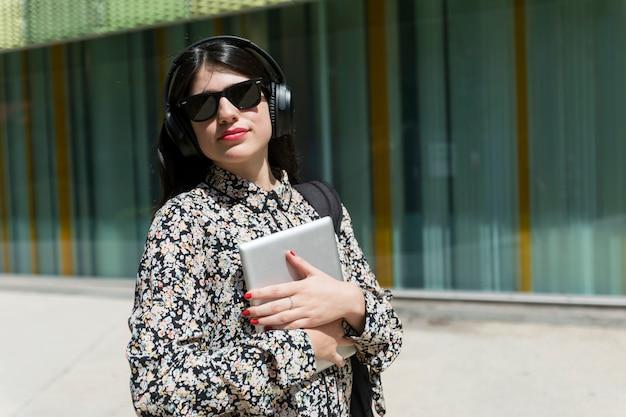 Belle femme tenant une tablette numérique en se tenant debout dans la rue