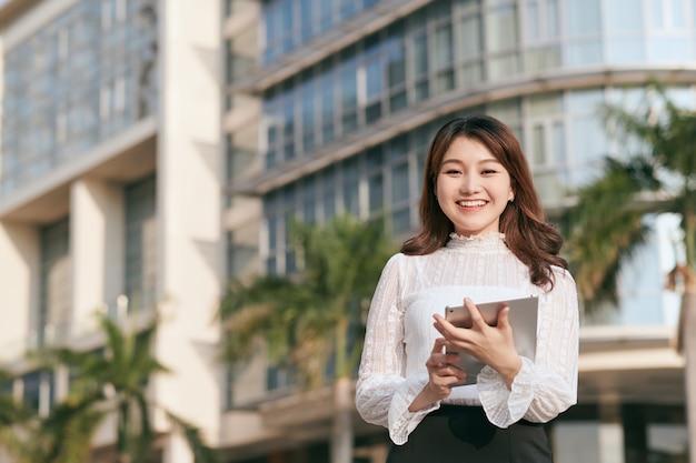 Belle femme tenant une tablette numérique tout en se tenant près d'un café