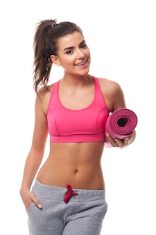Belle femme tenant un tapis d'exercice rose