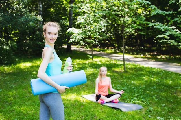 Belle femme tenant un tapis de yoga et une bouteille d'eau.