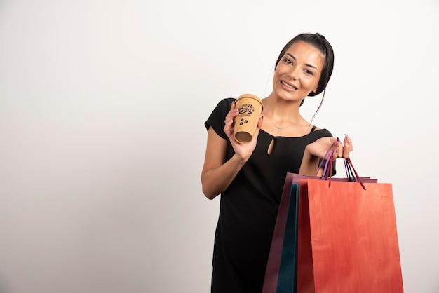 Belle femme tenant un tas de sacs à provisions et une tasse de café.