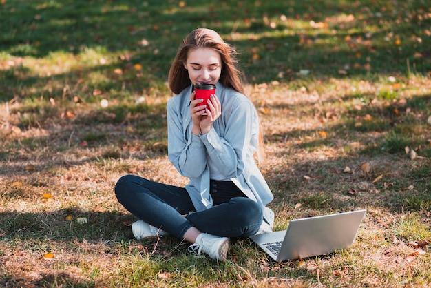 Belle femme tenant une tasse dans la nature