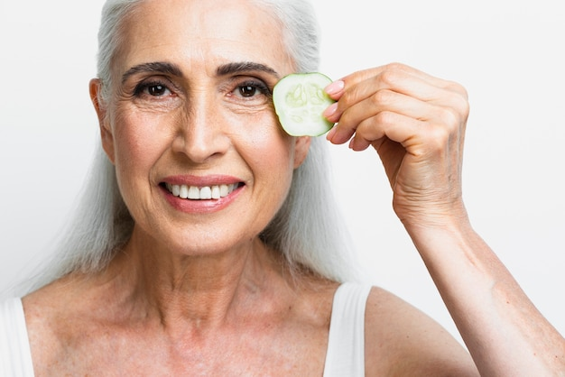 Belle femme tenant une tranche de concombre