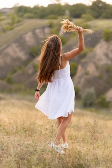 Belle femme tendre dans une robe d'été blanche se promène au coucher du soleil dans un champ avec un bouquet d'épillets.