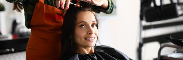 Belle femme tenir une mèche de cheveux et couper bang avec des ciseaux sur le lieu de travail