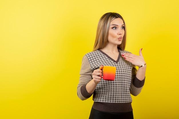 Belle femme en tenue décontractée tenant une tasse de thé.