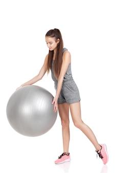 Belle femme en tenue de sport avec ballon de fitness isolé sur fond blanc