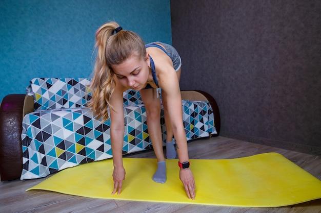 Belle femme en tenue de sport, short et soutien-gorge debout dans une pose, exercices, jolie fille pratiquant le yoga, s'entraînant à la maison ou dans un studio de yoga moderne, étirement du corps