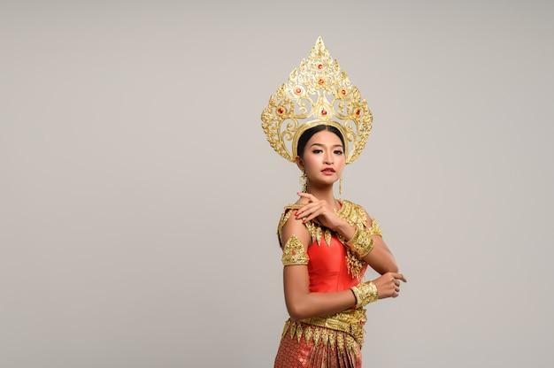 Belle femme thaïlandaise vêtue d'une robe thaïlandaise et regardant sur le côté