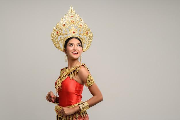 Belle femme thaïlandaise vêtue d'une robe thaïlandaise et regardant en haut