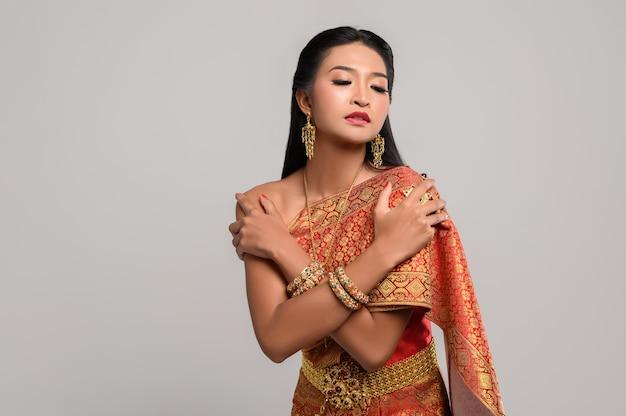 Belle femme thaïlandaise vêtue d'une robe thaïlandaise et se tenant dans ses bras