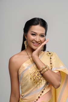 Belle femme thaïlandaise vêtue d'une robe thaïlandaise et d'un sourire heureux.