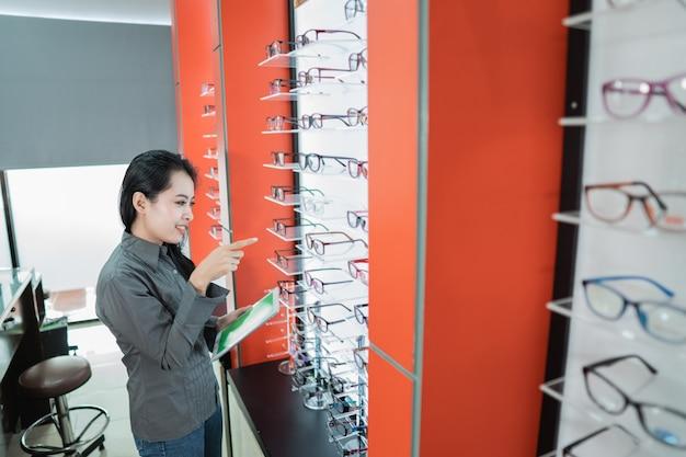 Une belle femme tient un catalogue de produits de lunettes disponibles après un examen de la vue dans une clinique ophtalmologique