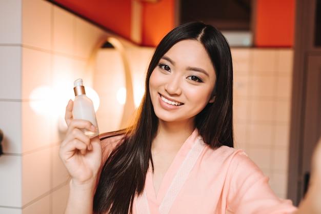 Belle femme tient des cosmétiques pour le visage