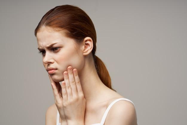 Belle femme touchant le visage avec la main mal de dents t-shirt blanc cheveux roux