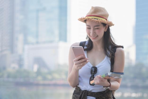 Belle femme touriste solo asiatique souriante et regardant un téléphone mobile