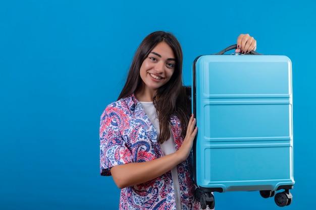 Belle femme touristique tenant une valise de voyage souriant joyeusement prêt à vacances debout sur un espace bleu isolé