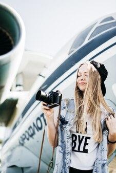 Belle femme touristique avec une vieille caméra vintage vintage posant près de l'avion