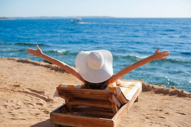 Belle femme en train de bronzer sur une plage dans une station balnéaire tropicale, profitant des vacances d'été en levant les mains.