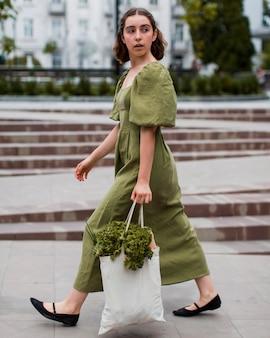 Belle femme transportant des produits d'épicerie bio
