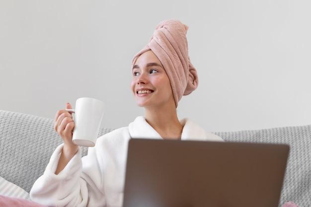 Belle femme travaillant après avoir pris un bain