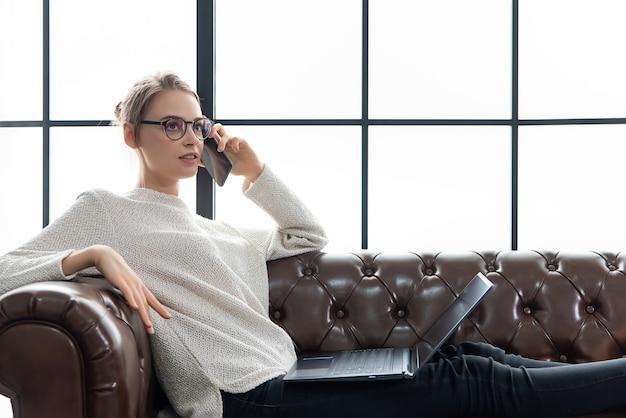Belle femme travaillant à la maison dans le salon confortable