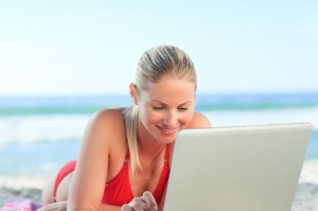 Belle femme travaillant sur son ordinateur portable à la plage