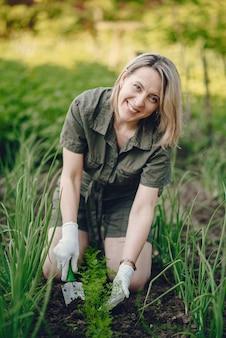 Belle femme travaille dans un jardin près de la maison