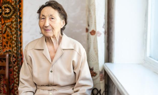 Belle femme très âgée à la maison près de la fenêtre