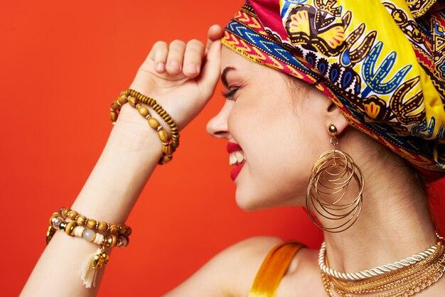 Belle femme en turban multicolore look attrayant bijoux fond isolé. photo de haute qualité