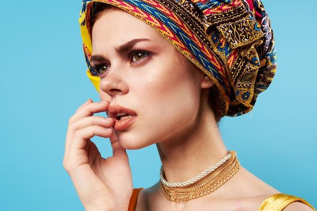 Belle femme en turban multicolore look attrayant bijoux sourire fond bleu
