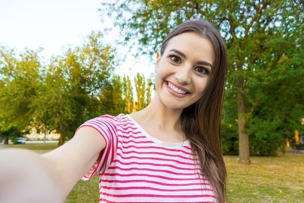 Belle femme urbaine prenant une photo d'elle-même, selfie.