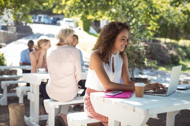 Belle femme utilisant un ordinateur portable au restaurant