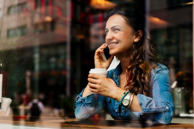 Belle femme utilisant son mobile dans un café.