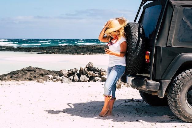 Belle femme utilisant un téléphone portable à la plage