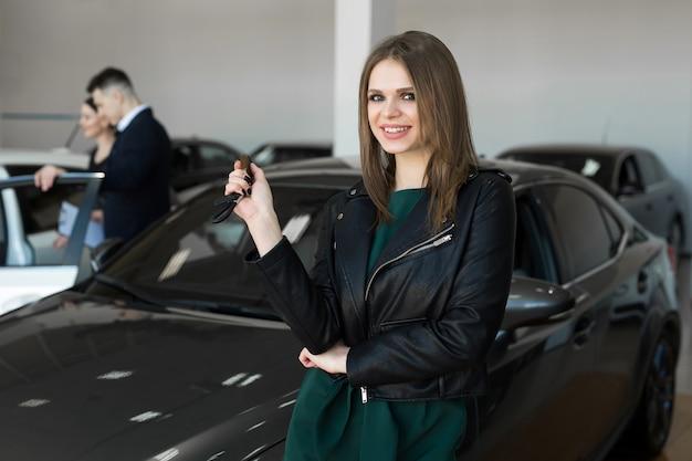 Belle femme ou vendeur de voiture stand tenant une nouvelle clé à distance de voiture dans une salle d'exposition de voiture